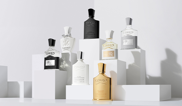 Aventus, Love In White, Silver Mountain Water, Green Irish Tweed, Millésime Impérial, Aventus For Her, and Aventus Cologne bottles on plexiglass platforms.